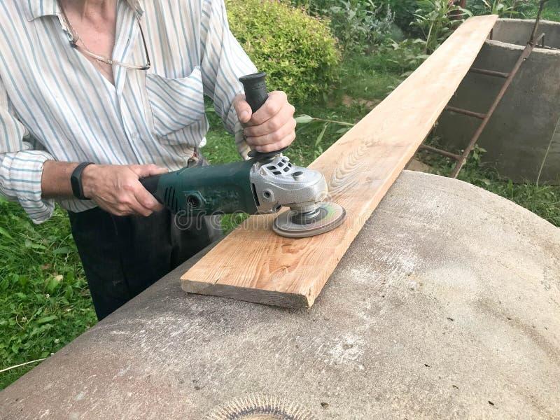 L'homme travaille avec ses mains, rectifie le disque autour pour la broyeur, l'outil électrique pour rectifier et polir la surfac image stock