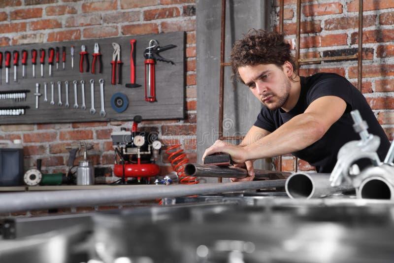 L'homme travaille dans un garage d'atelier à la maison avec du papier sablonneux à la surface de la conduite métallique sur le pu photographie stock libre de droits
