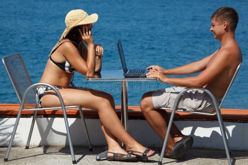 L'homme travaille pour l'ordinateur portatif. Fille parlant au téléphone. photographie stock libre de droits