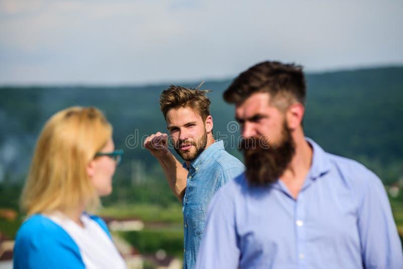 L'homme a trouvé ou a détecté l'amie le tricher marchant avec un autre homme Ami complètement des regards jaloux soupçonneusement photo stock