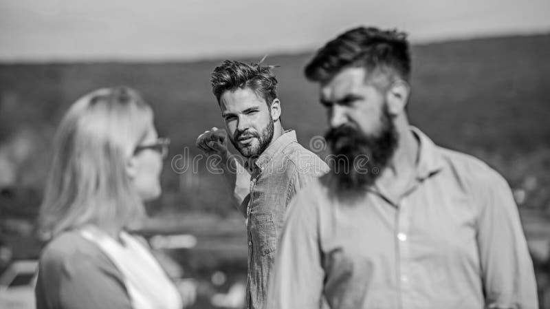 L'homme a trouvé ou a détecté l'amie le tricher marchant avec un autre homme Ami complètement des regards jaloux soupçonneusement photographie stock