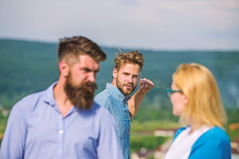 L'homme a trouv? ou a d?tect? l'amie le tricher marchant avec un autre homme Ami compl?tement des regards jaloux soup?onneusement photos libres de droits
