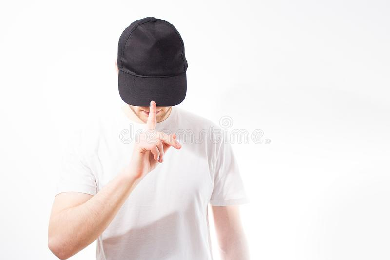 L'homme, type dans le noir vide, casquette de baseball, relance sur un wh image libre de droits