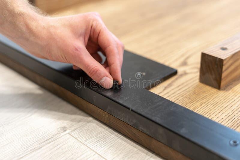 L'homme utilisant la vis attachent l'élément en métal sur le dessus de table en bois photo libre de droits