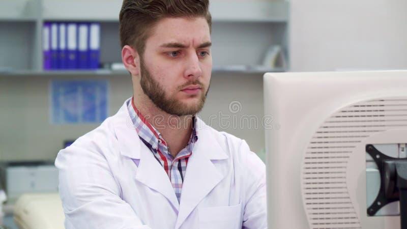 L'homme utilise l'ordinateur au laboratoire images stock