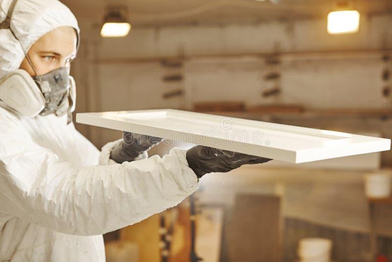 L'homme vérifie la régularité de l'application de peinture dans le masque respiratoire Application du feu s'assurant ignifuge image stock
