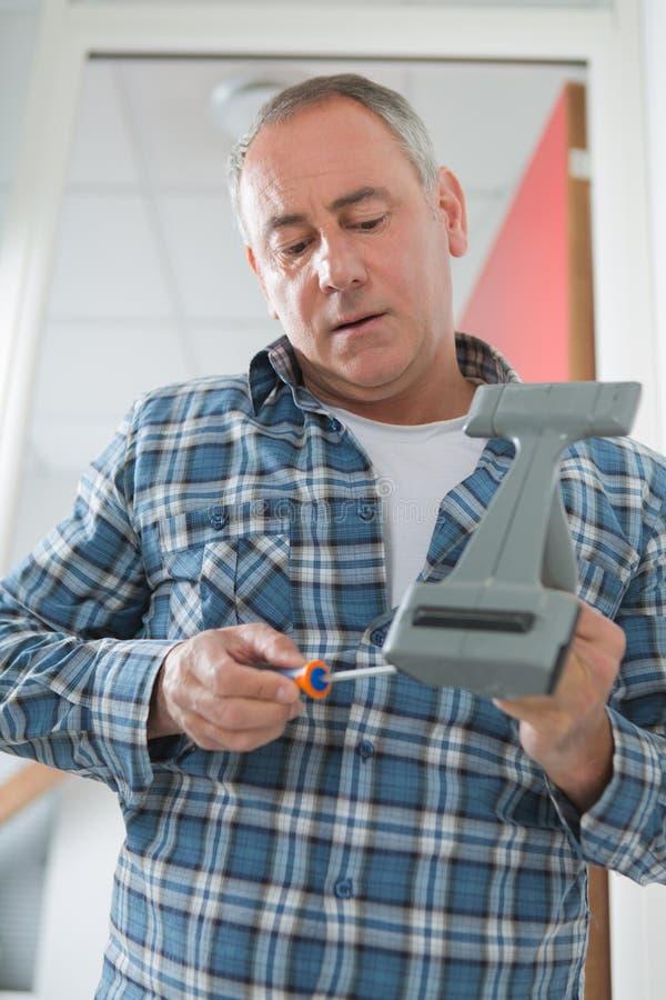 L'homme vérifie le dispositif cassé image stock