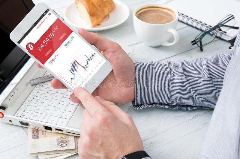 L'homme vérifie le taux de bitcoin à l'application du marché de forex photos libres de droits