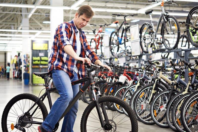 L'homme vérifie le vélo avant l'achat dans la boutique images libres de droits