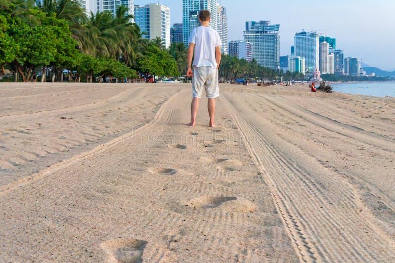 L'homme va loin sur la plage et il laisse des empreintes de pas sur le sable images libres de droits
