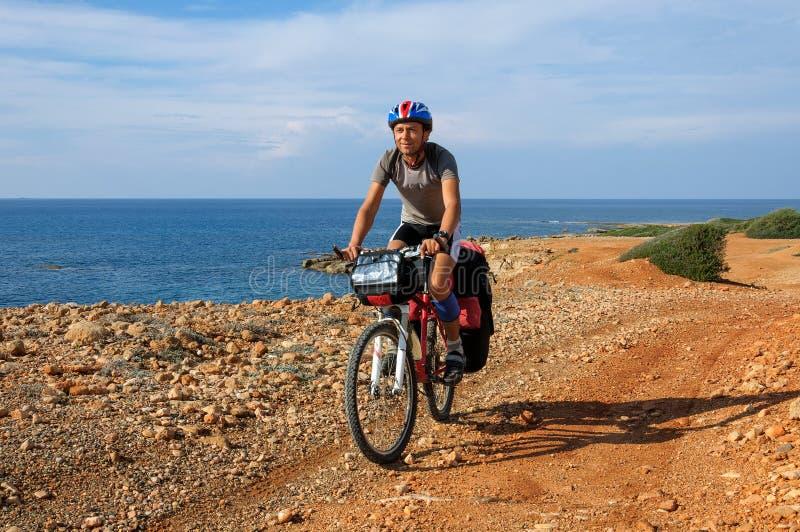 L'homme va plage sablonneuse sur le vélo de montagne avec le grand sac à dos image stock