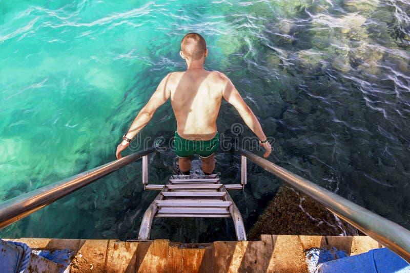 L'homme va sauter outre d'une jetée dans la mer photo libre de droits