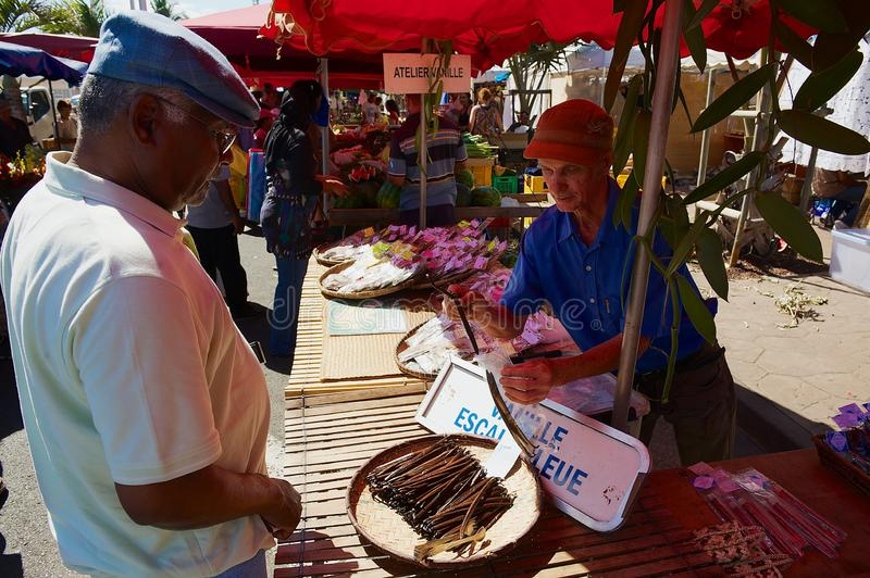 L'homme vend la vanille sèche au marché dans Saint Denis De La Reunion, France photo stock