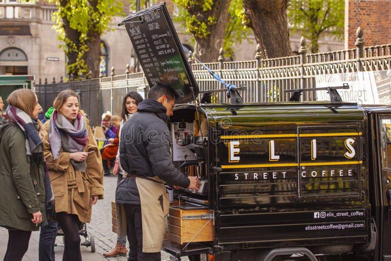 L'homme vend le cappucino, le café d'expresso et le thé frais dans un café mobile dans une petite voiture aux cutomers femelles photo stock