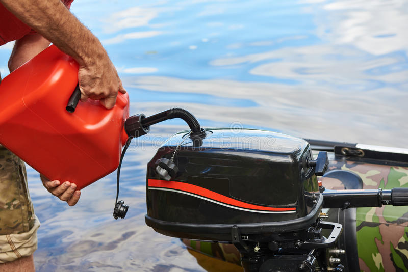L'homme verse l'essence dans le moteur du bateau de pêche image stock