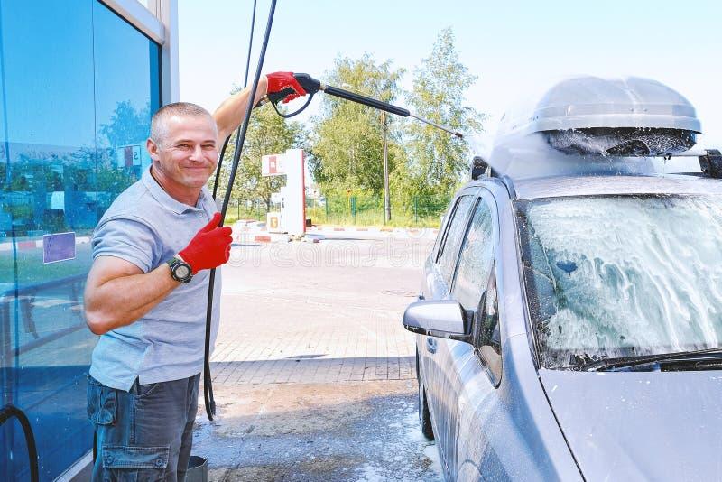 L'homme verse la carrosserie active de mousse Machine propre de Washington de v?hicule, lavage de voiture avec l'?ponge et boyau  images libres de droits