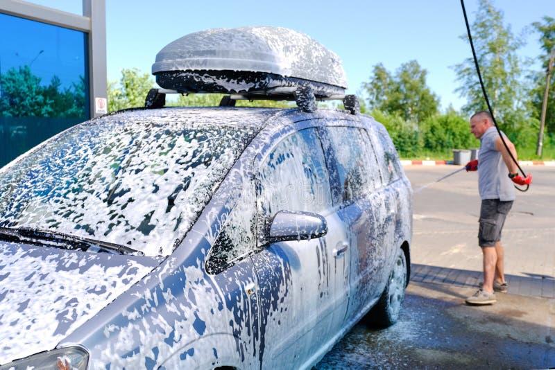 L'homme verse la carrosserie active de mousse Machine propre de Washington de v?hicule, lavage de voiture avec l'?ponge et boyau  photo stock