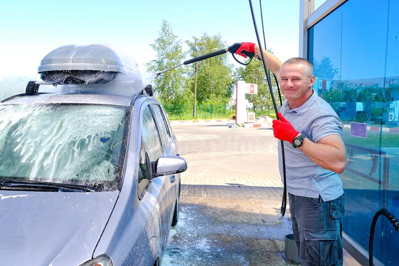 L'homme verse la carrosserie active de mousse Machine propre de Washington de v?hicule, lavage de voiture avec l'?ponge et boyau  photographie stock libre de droits