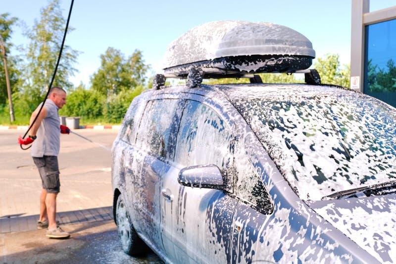 L'homme verse la carrosserie active de mousse Machine propre de Washington de v?hicule, lavage de voiture avec l'?ponge et boyau  image libre de droits