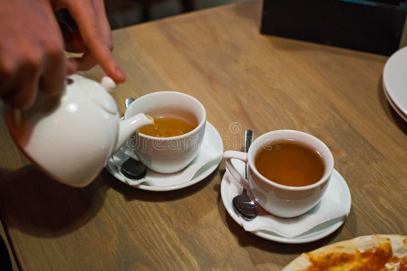 L'homme verse le thé de la théière dans la tasse blanche sur la table en bois La main d'homme versent le thé frais chaud photographie stock libre de droits