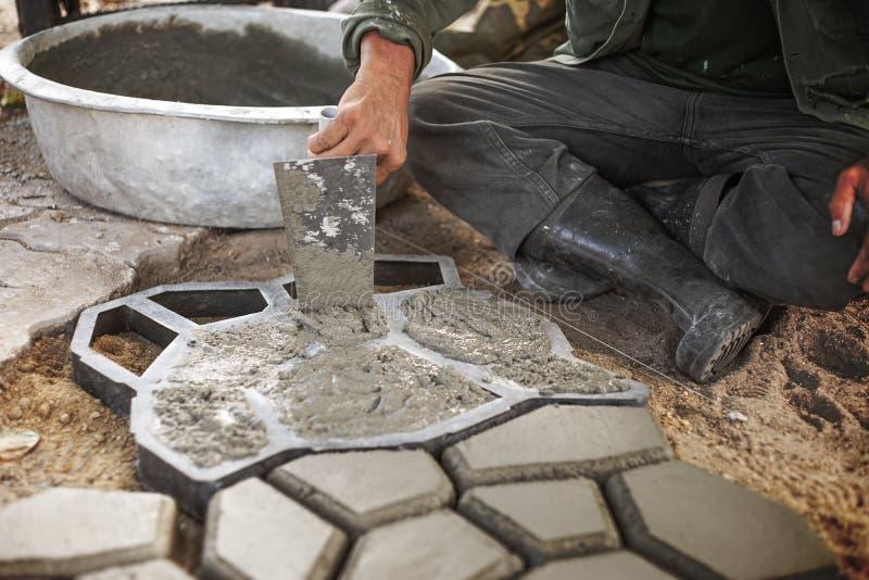 L'homme versent le ciment dedans à un moule pour faire Paversconcret image libre de droits