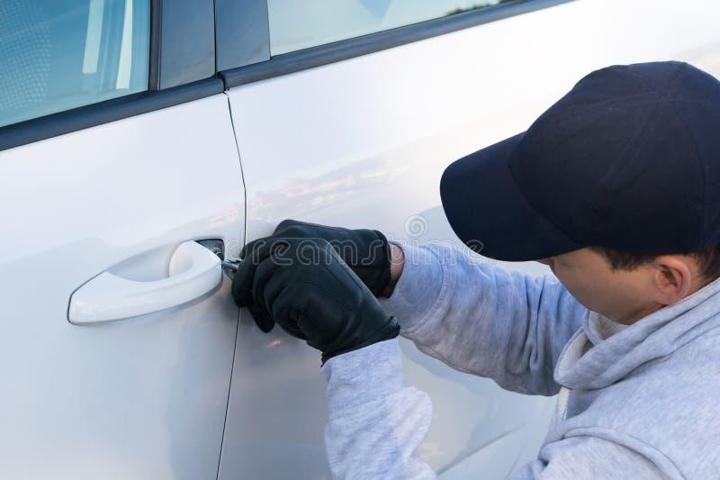 L'homme veut détourner une voiture, coupures dans la porte, vue arrière photos libres de droits