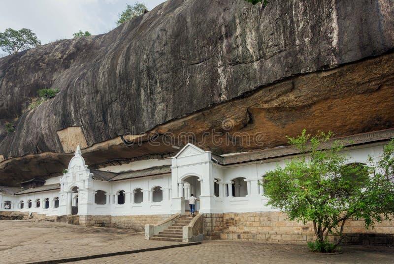 L'homme viennent à l'intérieur du temple historique de caverne dans Dambulla, Sri Lanka Site de patrimoine mondial de l'UNESCO à  image stock