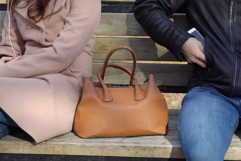 L'homme vole le téléphone d'un sac du ` s de femme en parc photo libre de droits