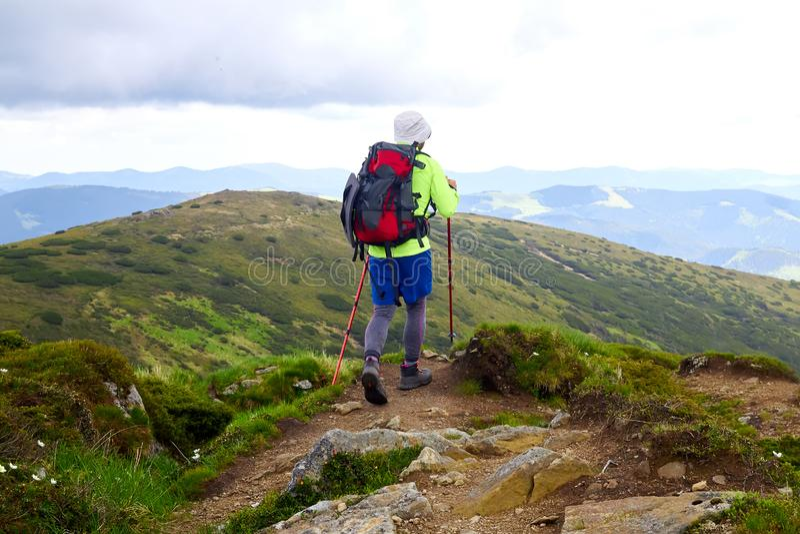 L'homme voyageant avec le sac à dos augmentant en montagnes voyagent des vacances actives d'aventure de concept de succès de mode photo stock