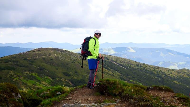 L'homme voyageant avec le sac à dos augmentant en montagnes voyagent des vacances actives d'aventure de concept de succès de mode image libre de droits