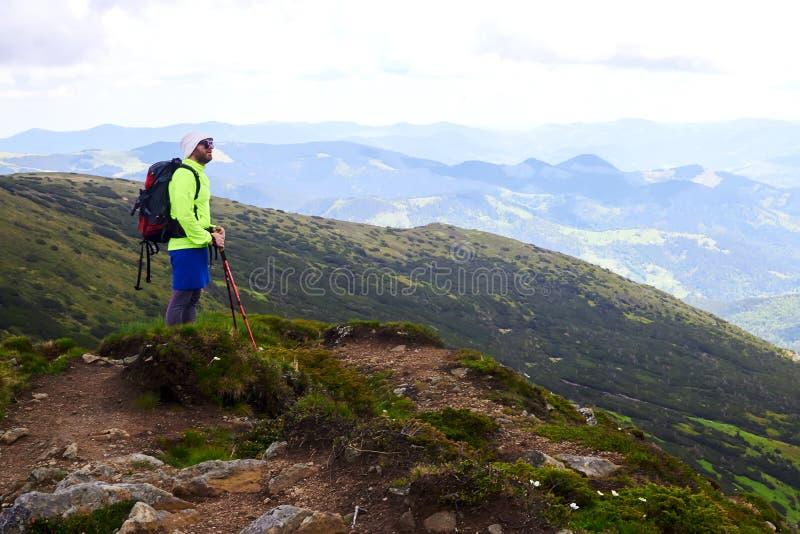 L'homme voyageant avec le sac à dos augmentant en montagnes voyagent des vacances actives d'aventure de concept de succès de mode photos libres de droits