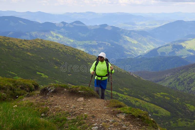 L'homme voyageant avec le sac à dos augmentant en montagnes voyagent des vacances actives d'aventure de concept de succès de mode photo libre de droits