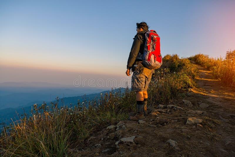 L'homme voyageant avec le sac à dos augmentant en montagnes voyagent mode de vie images stock