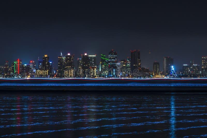 L'horizon routinier de San Diego la nuit avec la lumière traîne au-dessus de l'eau images stock
