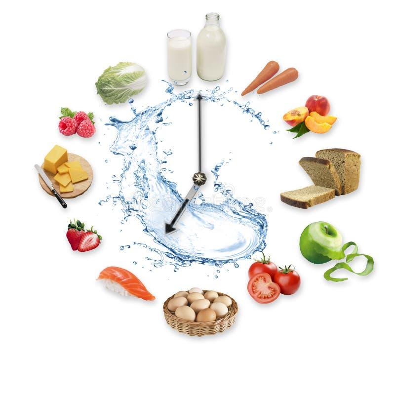 L'horloge a arrangé des produits alimentaires sains éclaboussent par l'eau d'isolement sur le fond blanc Concept sain de nourritu image stock