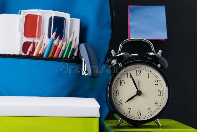 L'horloge prouve que son heure d'aller à l'école et aux choses d'école sur la table photo stock