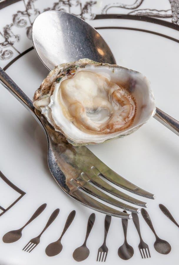 L'huître fraîche et juteuse crue ouverte a servi du plat en céramique de luxe photographie stock libre de droits