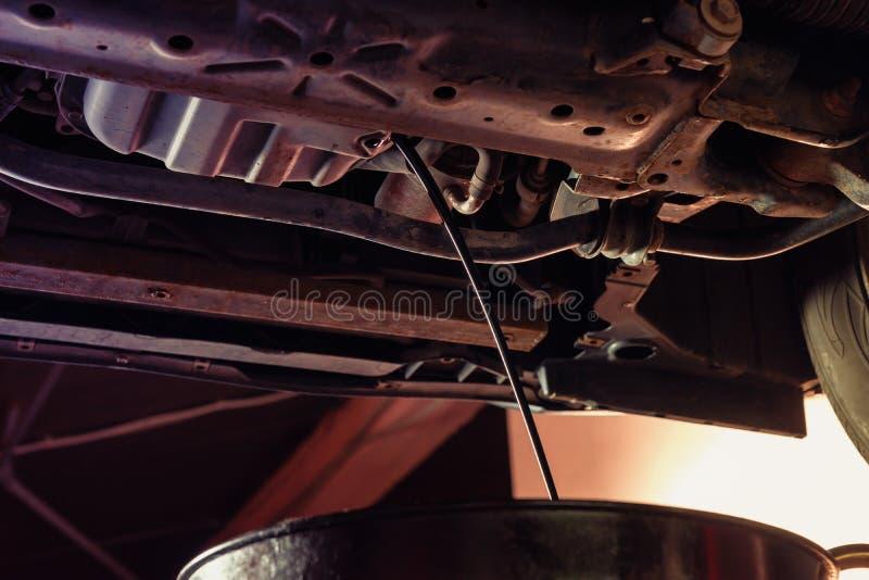 L'huile coule dans l'équipement pour l'huile de moteur changeante dans l'automobil photos libres de droits