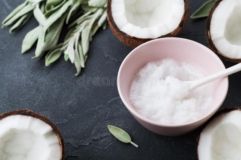 L'huile de noix de coco avec les noix de coco fraîches portent des fruits sur le fond en pierre noir Cosmétique naturel et organi photos stock
