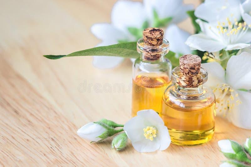 L'huile essentielle dans la bouteille en verre avec le jasmin frais fleurit, traitement de beauté Foyer sélectif de concept de st image stock