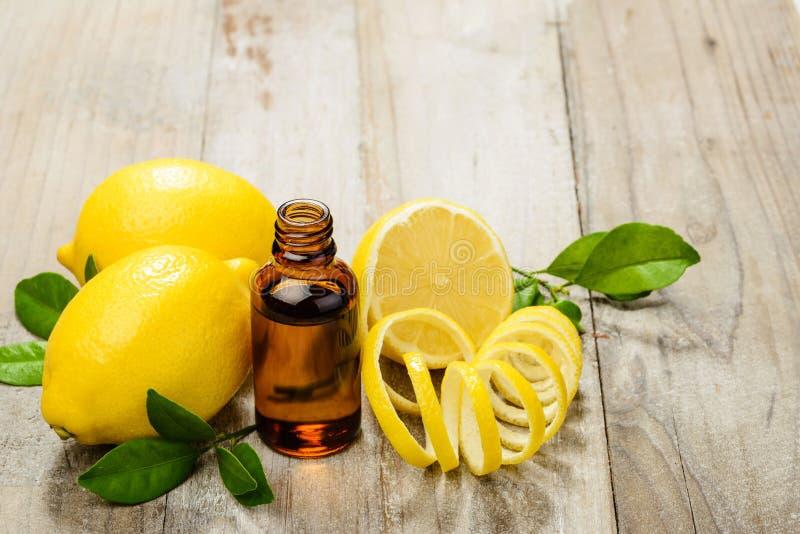 L'huile essentielle de citron et le citron portent des fruits sur le conseil en bois photographie stock