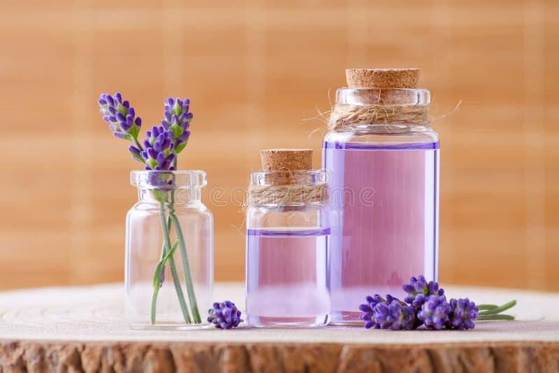 L'huile essentielle en bouteilles en verre et lavande fraîche fleurit sur le tronçon et le fond brun images stock