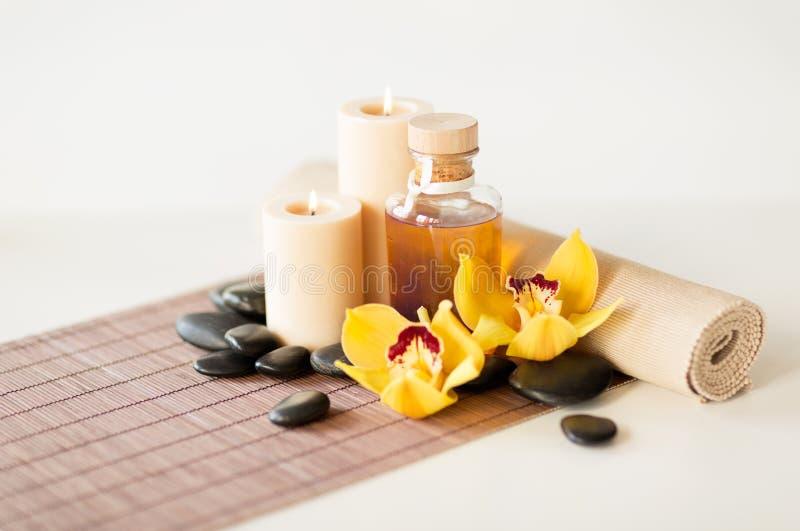 L'huile essentielle, les pierres de massage et l'orchidée fleurissent photos stock