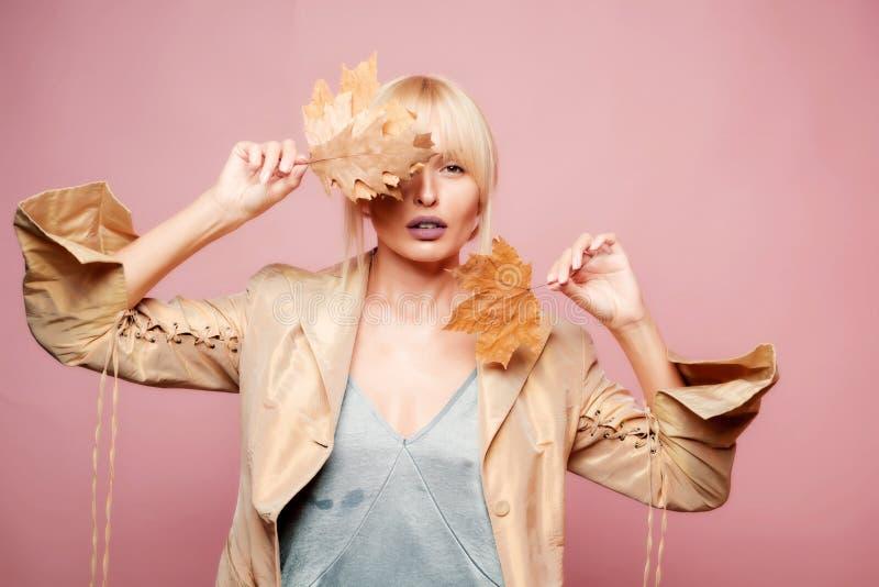 L'humeur d'automne et le temps sont chauds et ensoleillé et pluie est possible Étonnez la femme jouant avec des feuilles et regar photographie stock libre de droits