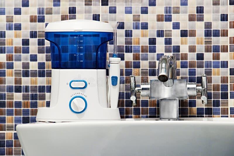 L'hygiène buccale, salle de bains objecte le concept Dites les dents du bout des lèvres nettoyant l'outil moderne d'irrigator sur photos stock