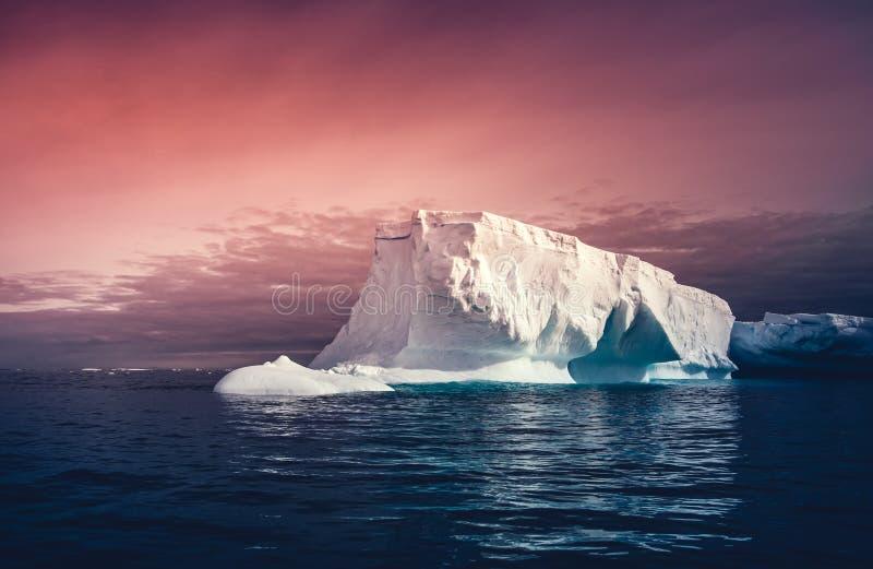 L'iceberg enorme sui precedenti variopinti del cielo fotografie stock libere da diritti