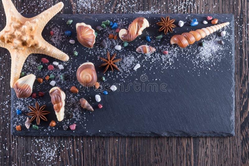 L'idée d'art de nourriture pour des enfants déjeunent ou dessert Bonbons au chocolat sous forme de fruits de mer sur le fond noir photographie stock libre de droits