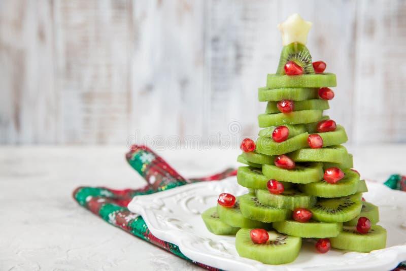 L'idée saine de dessert pour des enfants font la fête - l'arbre de Noël comestible drôle de grenade de kiwi images libres de droits
