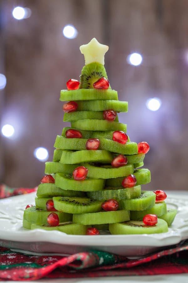 L'idée saine de dessert pour des enfants font la fête - l'arbre de Noël comestible drôle de grenade de kiwi photo stock