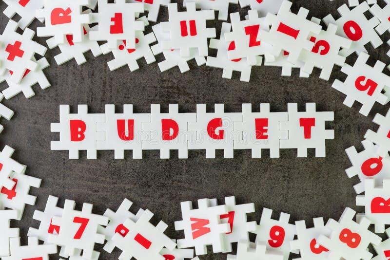 L'idea del bilancio, puzzle bianco di puzzle dell'abbondanza con gli alfabeti combina la parola BILANCIO e l'altro nero scuro del fotografie stock